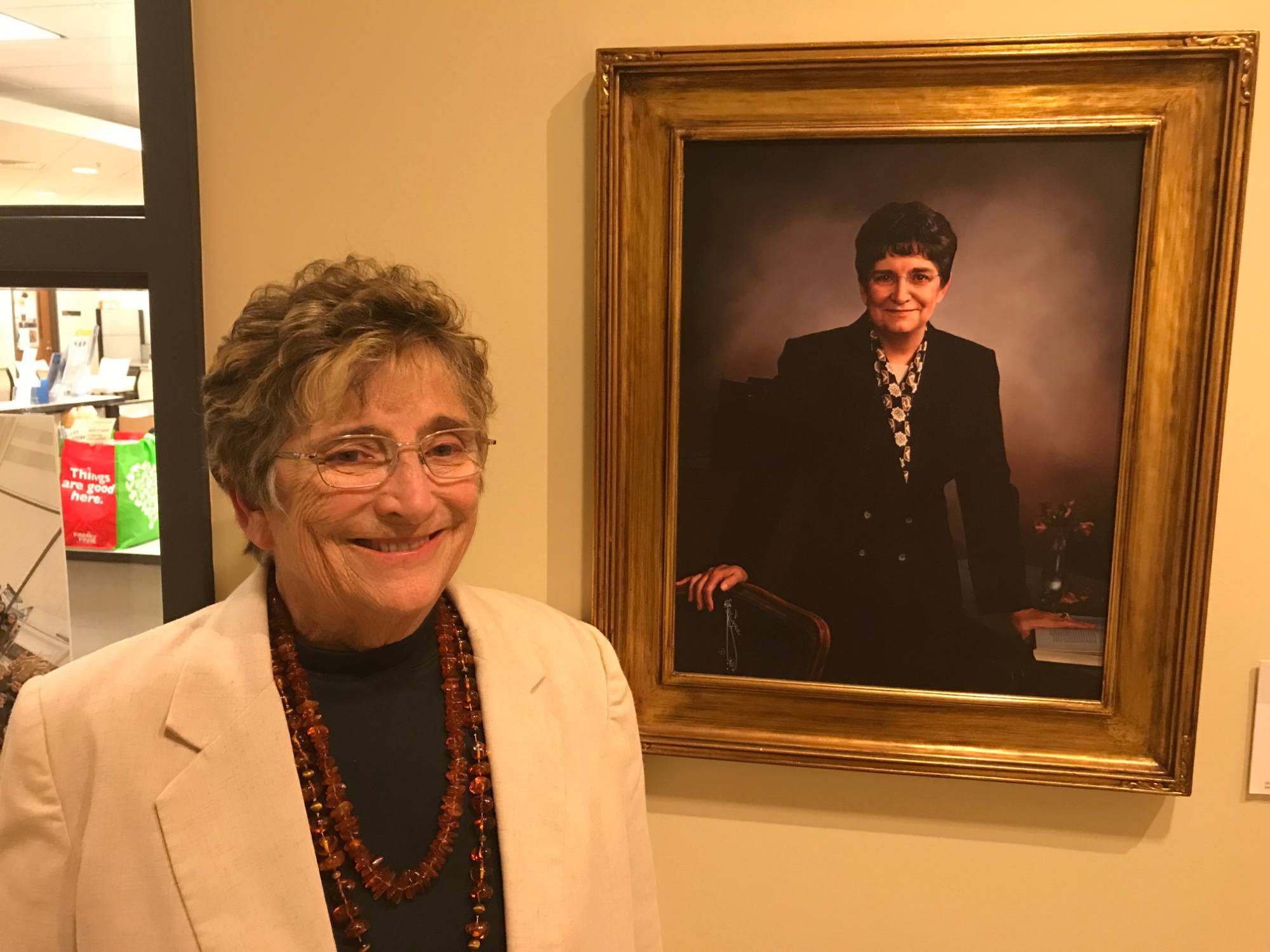 former Honors director Johnine Callahan smiling next to her hallway portrait